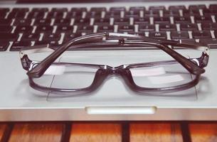 feche os óculos, o computador do escritório na mesa de trabalho, foto