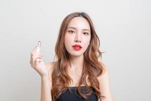 retrato linda mulher asiática fazendo maquiagem e usando batom vermelho em fundo branco foto