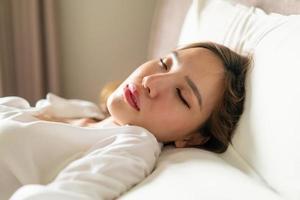 retrato linda mulher asiática dormindo na cama com travesseiro branco foto