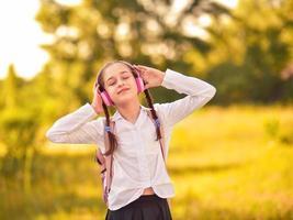 linda garotinha ouvindo música em fones de ouvido no parque outono foto
