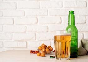 copo cheio de cerveja, garrafa e lanches, fundo de parede de tijolo branco foto