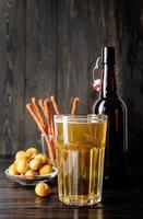 copo cheio de cerveja, garrafa e salgadinhos, fundo preto de madeira foto