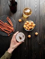 vista superior das mãos de uma mulher segurando um copo de cerveja, fundo preto de madeira foto