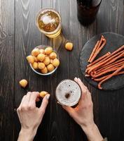 mulher com as mãos segurando um copo de cerveja e salgadinho de queijo no fundo preto foto