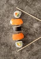 rolos de sushi colocados entre os pauzinhos em fundo escuro foto