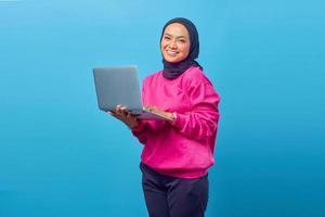 jovem feliz e sorridente segurando um laptop e enviando e-mail foto
