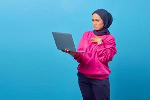 retrato de uma menina chocada e surpresa de pé e segurando um laptop foto