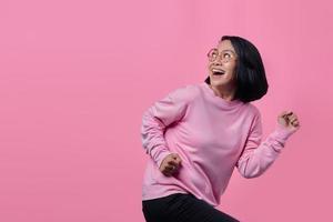 garota surpresa usando um macacão rosa isolado em um fundo de cor rosa foto