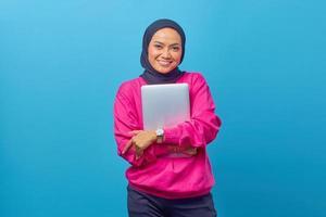 retrato de uma bela estudante universitária sorridente segurando um laptop foto