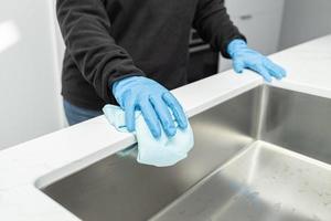 mãos na luva de proteção limpando uma pia moderna com pano foto