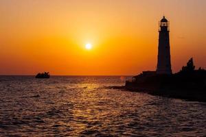 farol na costa do mar ao pôr do sol foto