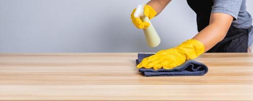 close-up do homem da limpeza trabalhando em uma loja limpa na mesa de madeira foto