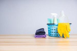 cesta de material de limpeza na mesa de madeira foto
