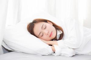 jovem mulher asiática dormindo deitada na cama no quarto. foto