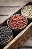 grãos de pimenta preta e vermelha branca orgânica em exposição de madeira foto