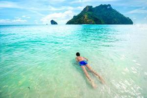 menino nadando e relaxando em um mar tropical límpido foto