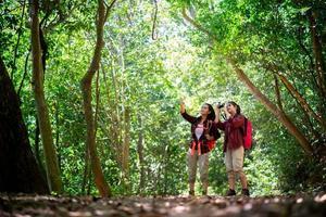 duas jovens asiáticas femininas hippie caminhando na floresta foto