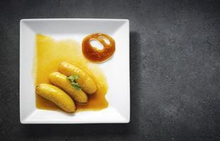 banana flambeed gourmet frita em molho de redução de suco de laranja e chip de caramelo de tangerina foto