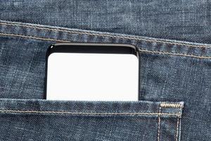 close-up de um smartphone no bolso da calça jeans com tela branca em branco foto
