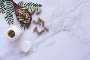 cápsula de ervas da natureza de ervas em mármore branco foto