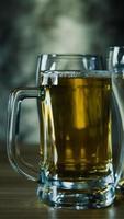 copos de cerveja escura, cerveja gelada artesanal em copo na mesa de madeira foto