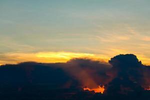 céu do pôr do sol de volta na nuvem escura buraco de lava vermelho do raio de sol última luz foto