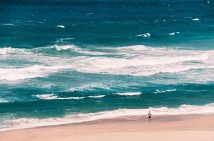 praia oceânica com ondas grandes, um pescador em pé com uma vara de pescar foto