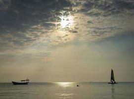 barco à vela no mar durante o pôr do sol na costa de phuket da tailândia foto