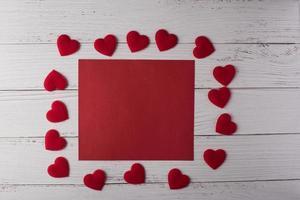 coração vermelho e cartão de nota vermelho em badkground de madeira branca. foto