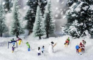conceito de natal de pessoas em miniatura se divertindo em um bosque de pinheiros foto