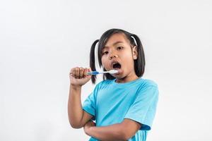 menina escovando os dentes em estúdio foto