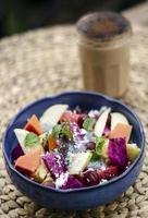 Salada de frutas tropicais asiáticas exóticas com sementes de manjericão e coco em uma tigela ao ar livre foto