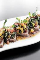 Salada gourmet moderna de fusão asiática com atum refogado e manga doce com soja picante e doce em restaurante de Singapura foto