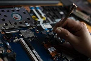 técnico de mão consertando notebook quebrado com uma chave de fenda foto