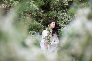 retrato de uma bela jovem no parque em ramos floridos foto