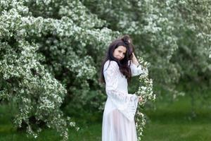 retrato de uma jovem no parque nos ramos floridos foto