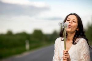 retrato de uma jovem morena com dente de leão em estrada de asfalto rural foto