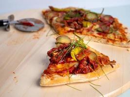 pizza vegetariana duas últimas peças, sobre uma mesa de madeira, fundo claro foto