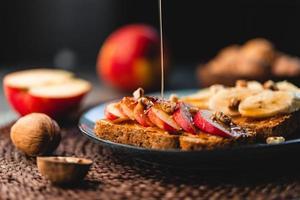 torradas com manteiga de amendoim, maçã, banana, nozes e mel foto