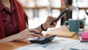 fechar mulher de negócios usando calculadora e laptop para fazer matemática foto