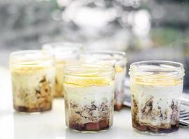 sobremesa de cheesecake vegan de maçã e coco orgânica em uma jarra de vidro em vitrine de café foto