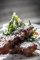 Espetos de porco assado na brasa com sementes de gergelim e molho de soja doce picante asiático em restaurante de Singapura foto