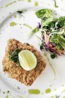 Filé de bacalhau empanado fresco frito almoço leve refeição de verão com arroz picante de vegetais mistos basco e salada foto