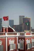 bandeiras da china e macau no prédio da sede do governo chinês no centro da cidade de macau foto