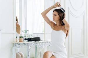 mulher desviando o olhar e penteando os cabelos enquanto se sente satisfeita foto