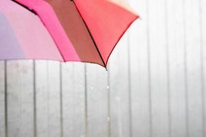 close-up da parte do guarda-chuva colorido com gotas de chuva foto