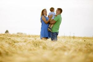 família jovem com garotinho fofo se divertindo ao ar livre no campo foto
