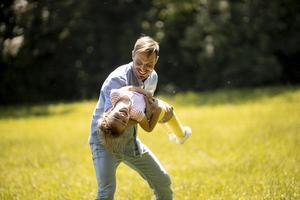 pai com filha se divertindo na grama do parque foto
