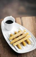 churros con chocolate tradicional espanhol doce café da manhã servido na mesa de madeira foto