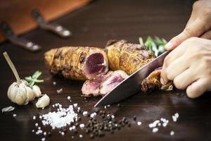 fatiar uma porção de rosbife orgânico com faca na mesa de madeira com alho, pimenta e sal em melbourne, austrália foto